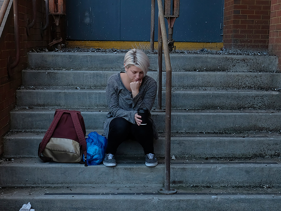 homeless woman sitting on stairs