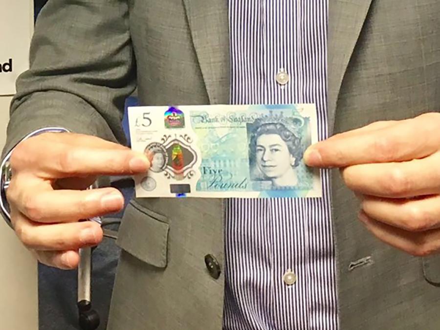 man holding up a five pound note