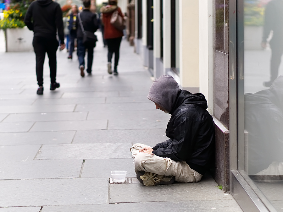 man sitting and begging in street