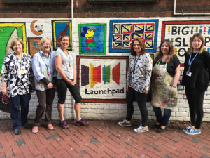 volunteer women standing in front of wall with launchpad logo on it