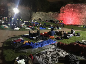people laying in on grass at night to raise money