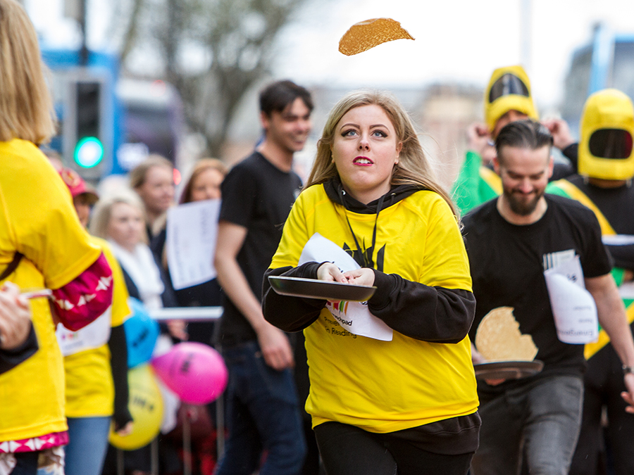 raise - woman flipping pancake in race